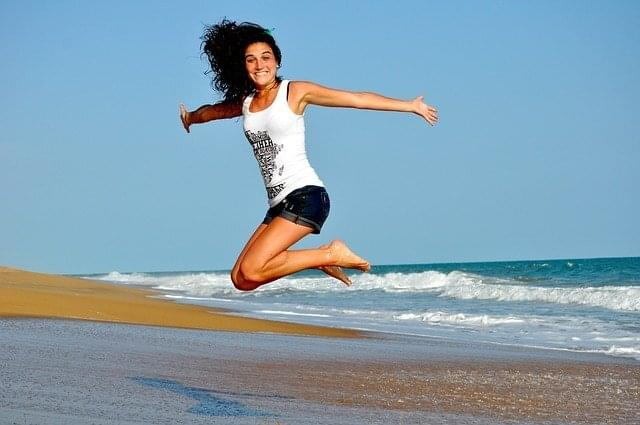 a happy woman jumping on the beach