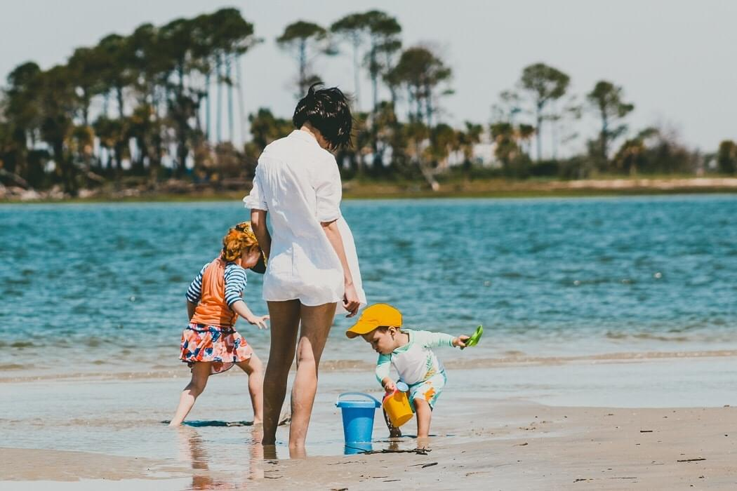 mother playing with her two children in the sand on the beach