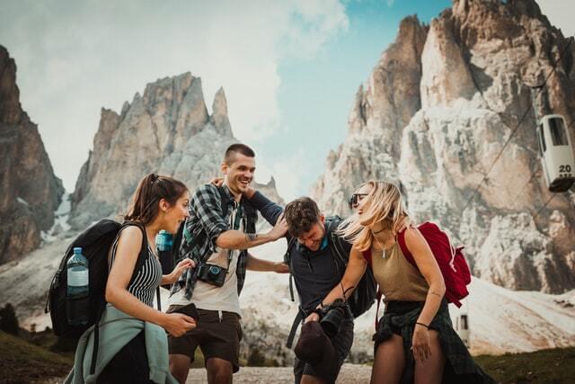 friends laughing while enjoying a trip through the mountains