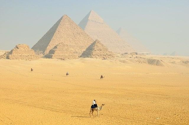 A person on a camel while admiring the pyramids of Egypt